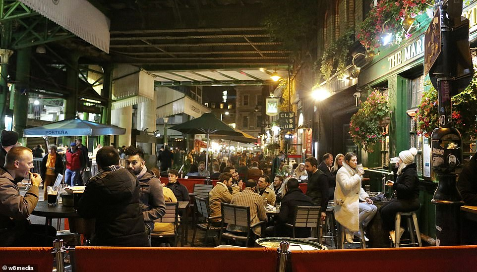 Under the new guidelines individuals from different households in London, Essex, York and parts of Derbyshire, will be banned from mixing indoors, even in hospitality venues. Pictured, people enjoy a drink in borough market