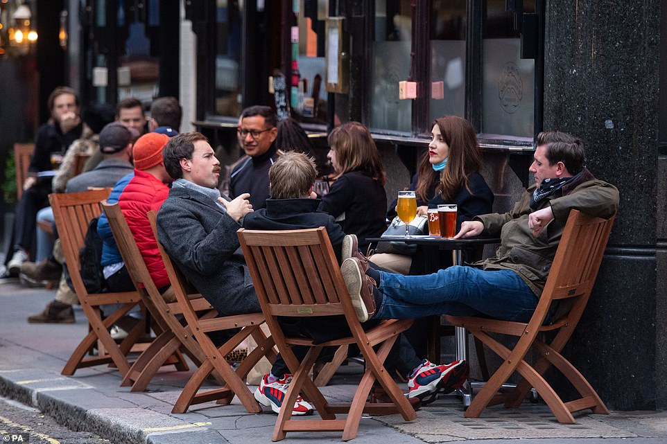 Drinkers outside a pub in Soho, London, on the first day after the city was put into Tier 2 restrictions to curb the spread of coronavirus