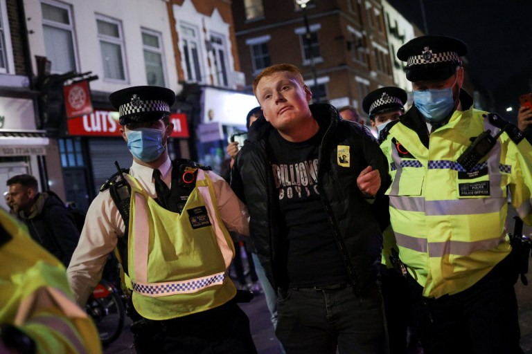 A man is detained by police officers in Soho, amid the outbreak of the coronavirus disease (COVID-19), in London, Britain October 16, 2020. REUTERS/Hannah McKay