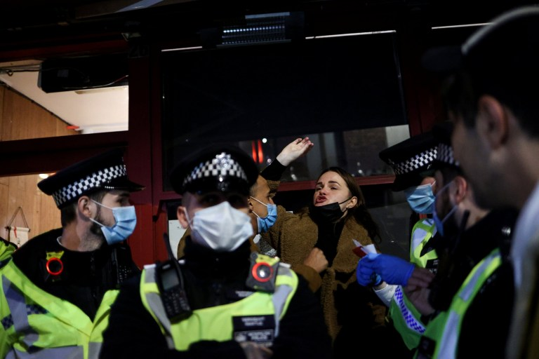 A woman shouts next to police officers in Soho, amid the outbreak of the coronavirus disease (COVID-19), in London, Britain October 16, 2020. REUTERS/Hannah McKay